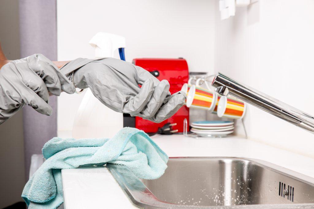putzhilfe-zieht-handschuhe-vor-der-grundreinigung-an