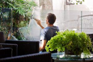 reinigungskraft-reinigt-glas-und-fenster-in-einem-restaurant